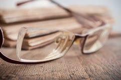 Γυαλιά στο αρχαίο βιβλίο ανοικτό στο ξύλινο επιτραπέζιο backgrou Στοκ εικόνες με δικαίωμα ελεύθερης χρήσης