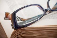 Γυαλιά στο αρχαίο βιβλίο ανοικτό στο ξύλινο επιτραπέζιο backgrou Στοκ Εικόνες