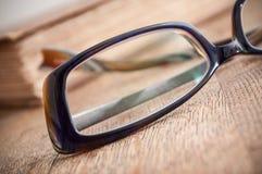Γυαλιά στο αρχαίο βιβλίο ανοικτό στο ξύλινο επιτραπέζιο backgrou Στοκ Φωτογραφία