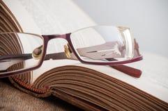 Γυαλιά στο αρχαίο βιβλίο ανοικτό στο ξύλινο επιτραπέζιο backgrou Στοκ φωτογραφίες με δικαίωμα ελεύθερης χρήσης
