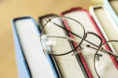 Γυαλιά στο ζωηρόχρωμο βιβλίο στοκ εικόνες