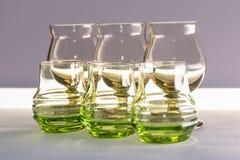 Γυαλιά του γυαλιού για το κρασί και των κοκτέιλ στον πίνακα σε ένα άσπρο υπόβαθρο Στοκ Εικόνες
