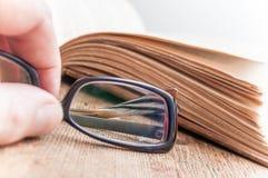 Γυαλιά υπό εξέταση στο αρχαίο βιβλίο ανοικτό στον ξύλινο πίνακα Στοκ Εικόνες