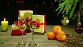 Γυαλιά CHAMPAGNE δίπλα στο χριστουγεννιάτικο δέντρο και δώρα σε έναν ξύλινο πίνακα σε ένα μαύρο υπόβαθρο με τα φω'τα φιλμ μικρού μήκους
