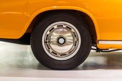 Γυαλισμένο πλαίσιο αυτοκινήτων με τη μαύρη εκλεκτής ποιότητας ρόδα στο πορτοκαλί αυτοκίνητο στοκ εικόνες