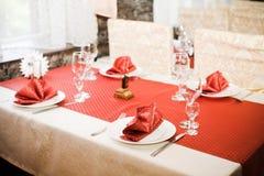 Γυαλί επιτραπέζιου σκεύους στον πίνακα και το κόκκινο τραπεζομάντιλο Στοκ Εικόνες