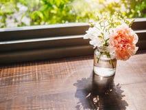 Γυαλί διακοσμήσεων γαρίφαλων λουλουδιών στο ξύλινο ντεκόρ επιτραπέζιων σπιτιών Στοκ Εικόνες