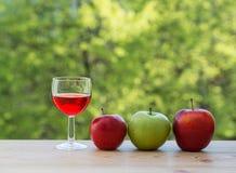 Γυαλί κρασιού και ζωηρόχρωμα μήλα στον πίνακα Στοκ εικόνα με δικαίωμα ελεύθερης χρήσης