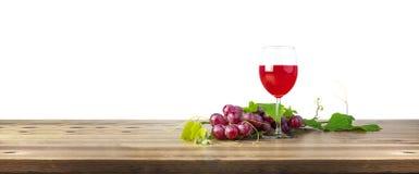 Γυαλί κόκκινου κρασιού και δέσμη των σταφυλιών στον ξύλινο πίνακα Στοκ Εικόνα