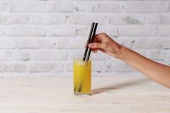 Γυαλί με τον πάγο και το χυμό από πορτοκάλι Γυναίκα που πίνει το χυμό Στοκ Εικόνα