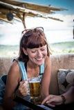 Γυαλί μπύρας εκμετάλλευσης γυναικών, κινηματογράφηση σε πρώτο πλάνο, στο υπαίθριο εσωτερικό υπόβαθρο φραγμών, Μπαλί, Ινδονησία, θ στοκ φωτογραφία