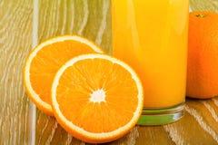 Γυαλί χυμού από πορτοκάλι με το πορτοκάλι και τα μισά Στοκ Φωτογραφίες