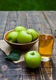 Γυαλί χυμού της Apple με τα υγιή πράσινα μήλα στο ξύλινο κύπελλο Στοκ Εικόνα