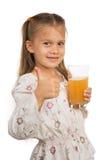 Γυαλί Holdng κοριτσιών με το χυμό της Apple που παρουσιάζει αντίχειρα Στοκ Φωτογραφίες