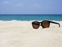Γυαλιά ήλιων στο διακινούμενο υπόβαθρο καλοκαιρινών διακοπών παραλιών άμμου Στοκ φωτογραφίες με δικαίωμα ελεύθερης χρήσης