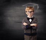 Γυαλιά αγοριών παιδιών, εκπαίδευση πινάκων καπέλων κιμωλίας σχολικών παιδιών στοκ φωτογραφίες