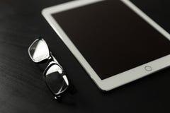 Γυαλιά ανάγνωσης και υπολογιστής ταμπλετών στο μαύρο γραφείο στοκ φωτογραφία με δικαίωμα ελεύθερης χρήσης