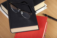 Γυαλιά ανάγνωσης που βάζουν πάνω από έναν σωρό των βιβλίων Στοκ Εικόνα