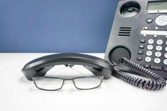 Γυαλιά ατόμων στο γραφείο γραφείων με το τηλέφωνο IP Στοκ φωτογραφία με δικαίωμα ελεύθερης χρήσης