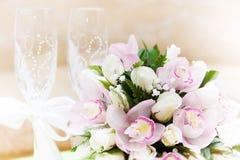 Γυαλιά γαμήλιων ανθοδεσμών και κρασιού στο υπόβαθρο Στοκ Εικόνες