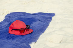 Γυαλιά ηλίου, μια ΚΑΠ και μια πετσέτα στην παραλία στοκ φωτογραφία με δικαίωμα ελεύθερης χρήσης