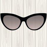 Γυαλιά ηλίου σε ένα μαύρο πλαίσιο σε ένα άσπρο ξύλινο υπόβαθρο απεικόνιση αποθεμάτων