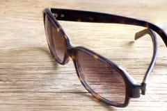 Γυαλιά ηλίου σε μια ξύλινη επιτραπέζια κινηματογράφηση σε πρώτο πλάνο Στοκ Εικόνες