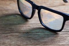 Γυαλιά ηλίου σε μια ξύλινη επιτραπέζια κινηματογράφηση σε πρώτο πλάνο Στοκ εικόνα με δικαίωμα ελεύθερης χρήσης