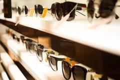 Γυαλιά ηλίου στα ελαφριά ράφια Στοκ Εικόνες
