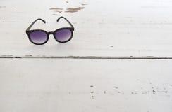 Γυαλιά ηλίου στην άσπρη χρωματισμένη επιφάνεια Στοκ Φωτογραφίες