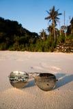 Γυαλιά ηλίου στην αμμώδη παραλία πέρα από το τροπικό υπόβαθρο νησιών Στοκ Εικόνες