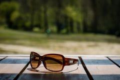 Γυαλιά ηλίου στον πίνακα στον ήλιο σε έναν ξύλινο πίνακα στοκ φωτογραφία