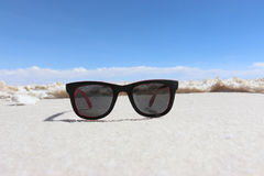 Γυαλιά ηλίου στο αλατισμένο υπόβαθρο λιμνών θηλυκή τοποθέτηση στρώματος λιμνών της Βολιβίας de distance 01 06 2000 απομονωμένη απ Στοκ Φωτογραφίες