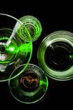 Γυαλιά και γυαλιά που τονίζονται από το χρωματισμένο φως σε ένα μαύρο υπόβαθρο Στοκ Εικόνες