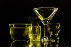 Γυαλιά και γυαλιά που τονίζονται από το χρωματισμένο φως σε ένα μαύρο υπόβαθρο Στοκ Φωτογραφίες
