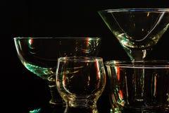 Γυαλιά και γυαλιά που τονίζονται από το χρωματισμένο φως σε ένα μαύρο υπόβαθρο Στοκ φωτογραφία με δικαίωμα ελεύθερης χρήσης