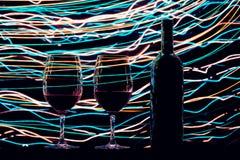 Γυαλιά και μπουκάλι κρασιού στο μαύρα υπόβαθρο και τα ίχνη Στοκ εικόνα με δικαίωμα ελεύθερης χρήσης
