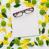Γυαλιά και φύλλο του εγγράφου με το σχέδιο από τα πέταλα των λουλουδιών Στοκ Φωτογραφία