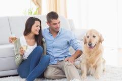 Γυαλιά κρασιού εκμετάλλευσης ζεύγους εξετάζοντας το σκυλί Στοκ φωτογραφία με δικαίωμα ελεύθερης χρήσης