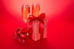 Γυαλιά κρασιού με τη σαμπάνια, δώρα Χριστουγέννων Στοκ Φωτογραφία