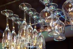 Γυαλιά κρασιού που κρεμούν επάνω από το ράφι φραγμών Στοκ Εικόνες