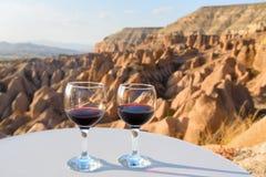 Γυαλιά κόκκινου κρασιού στο κόκκινο υπόβαθρο κοιλάδων σε Cappadocia Τουρκία Στοκ Φωτογραφία
