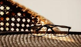 Γυαλιά πάνω από τα έπιπλα ινδικού καλάμου, στο σύγχρονο σπίτι με τον τρύγο Στοκ Φωτογραφία