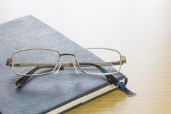 Γυαλιά που τίθενται στο βιβλίο κειμένων Στοκ Εικόνα