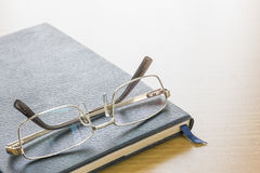 Γυαλιά που τίθενται στο βιβλίο κειμένων Στοκ Εικόνες