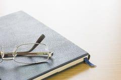 Γυαλιά που τίθενται στο βιβλίο κειμένων Στοκ φωτογραφίες με δικαίωμα ελεύθερης χρήσης