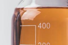 Γυαλικά με την κλίμακα με τα χρωματισμένα υγρά, έννοια εργαστηριακού εξοπλισμού, μακροεντολή Στοκ Εικόνες