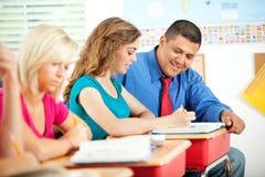 Γυμνάσιο: Ισπανικός δάσκαλος που βοηθά τη γυναίκα σπουδαστή στοκ εικόνες
