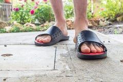 Γυμνά πόδια του αγοριού στις μαύρες παντόφλες στοκ εικόνες