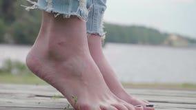 Γυμνά πόδια του κοριτσιού που στέκονται στα toe ακρών και που προσπαθούν να κρατήσει την ισορροπία στην ξύλινη πορεία φιλμ μικρού μήκους